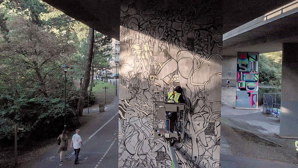 Graffiti artist on cherry picker at Upside Gallery