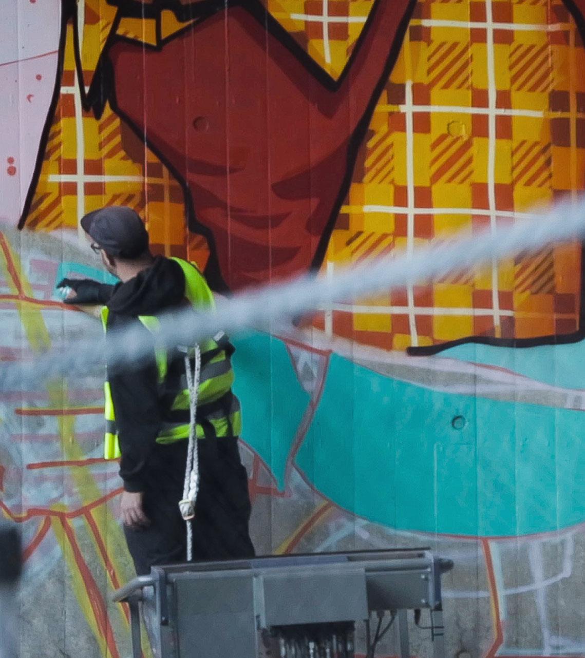Alex Odisy tattoo artist painting graffiti mural