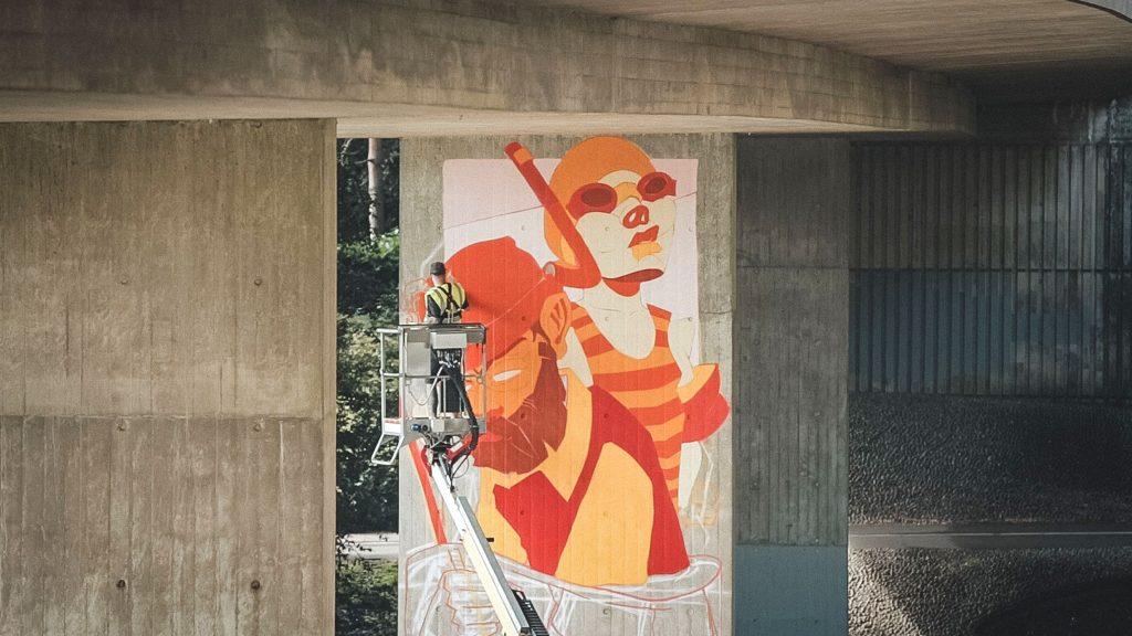 Graffiti artist Odisy painting mural on boom lift