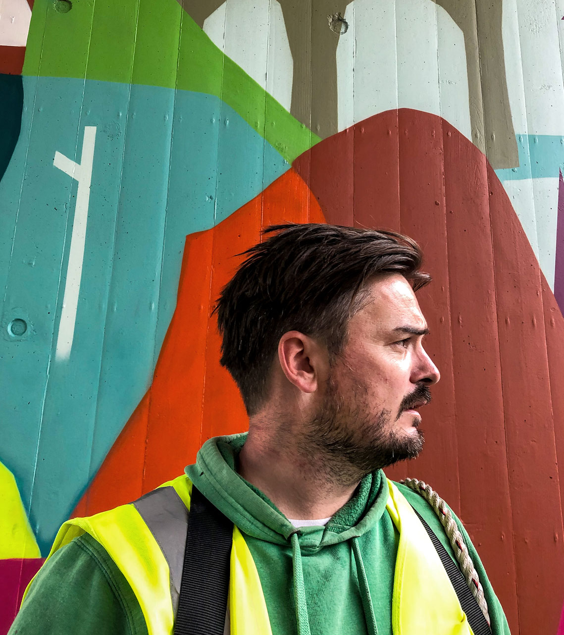 Graffiti artist Squirl in front of mural at Upside Gallery